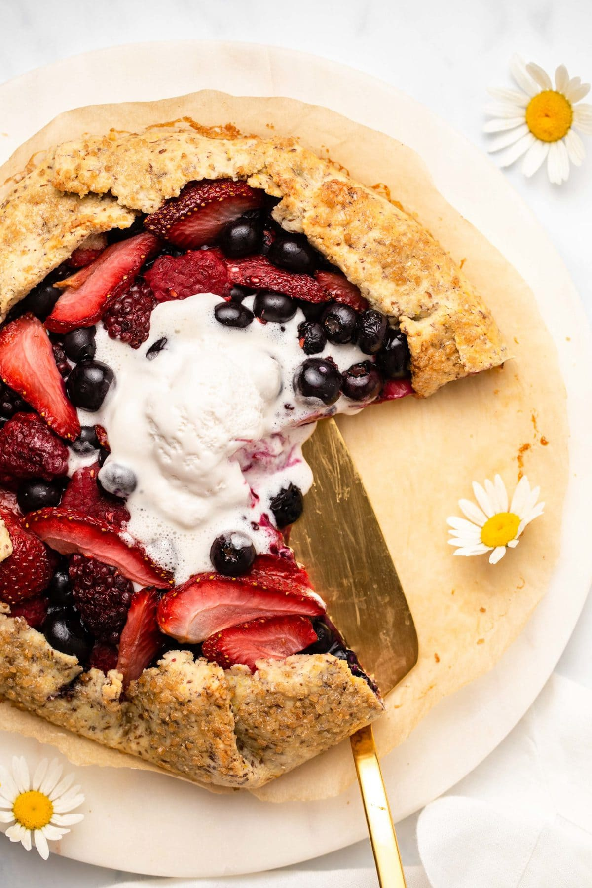 Baked berry galette with scoop of melting vanilla ice cream on top. A gold pie server is off to the side with a few daisies.