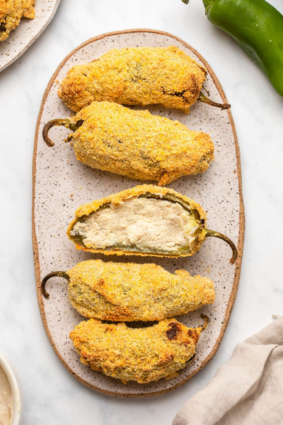 """Small plate of 5 jalapeño poppers, with one of them sliced in half to show the vegan """"cream cheese"""" filling"""