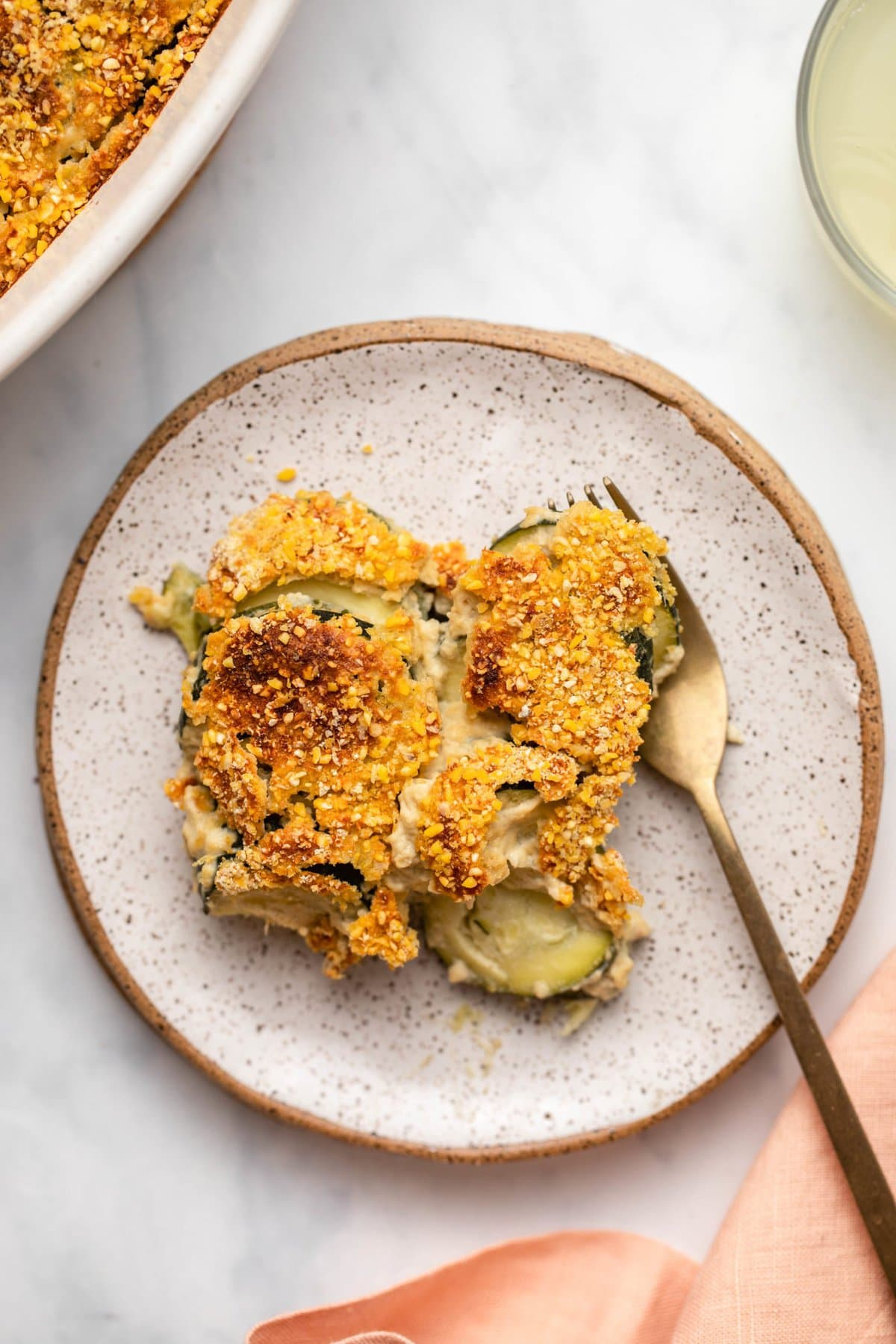 Close-up photo of zucchini gratin on small white plate with gold fork