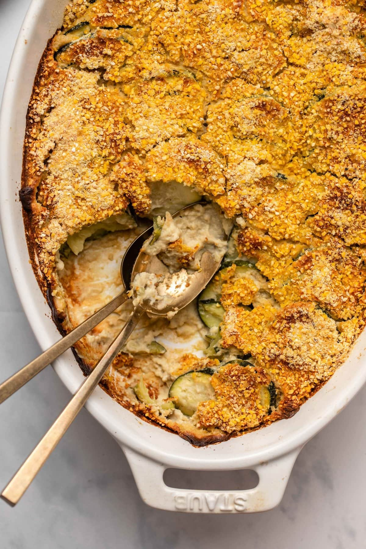 Close-up photo of zucchini gratin in white casserole dish with a scoop taken out of it