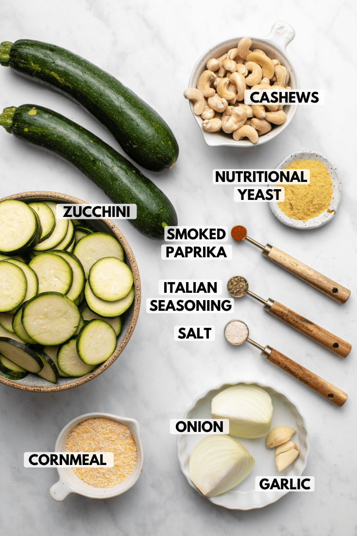 Ingredients for zucchini gratin arranged on marble countertop. Clockwise text labels read cashews, nutritional yeast, smoked paprika, italian seasoning, salt, onion, garlic, cornmeal, and zucchini