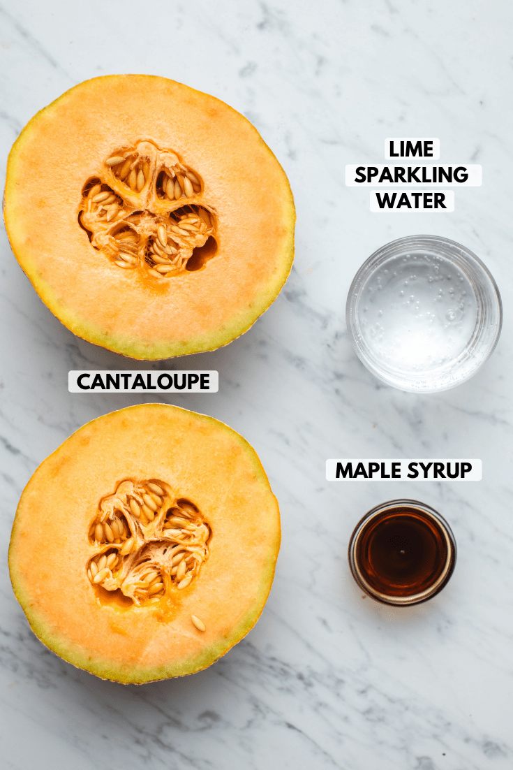 Ingredients for cantaloupe slushie on marble background; clockwise text labels read lime sparkling water, maple syrup, and cantaloupe
