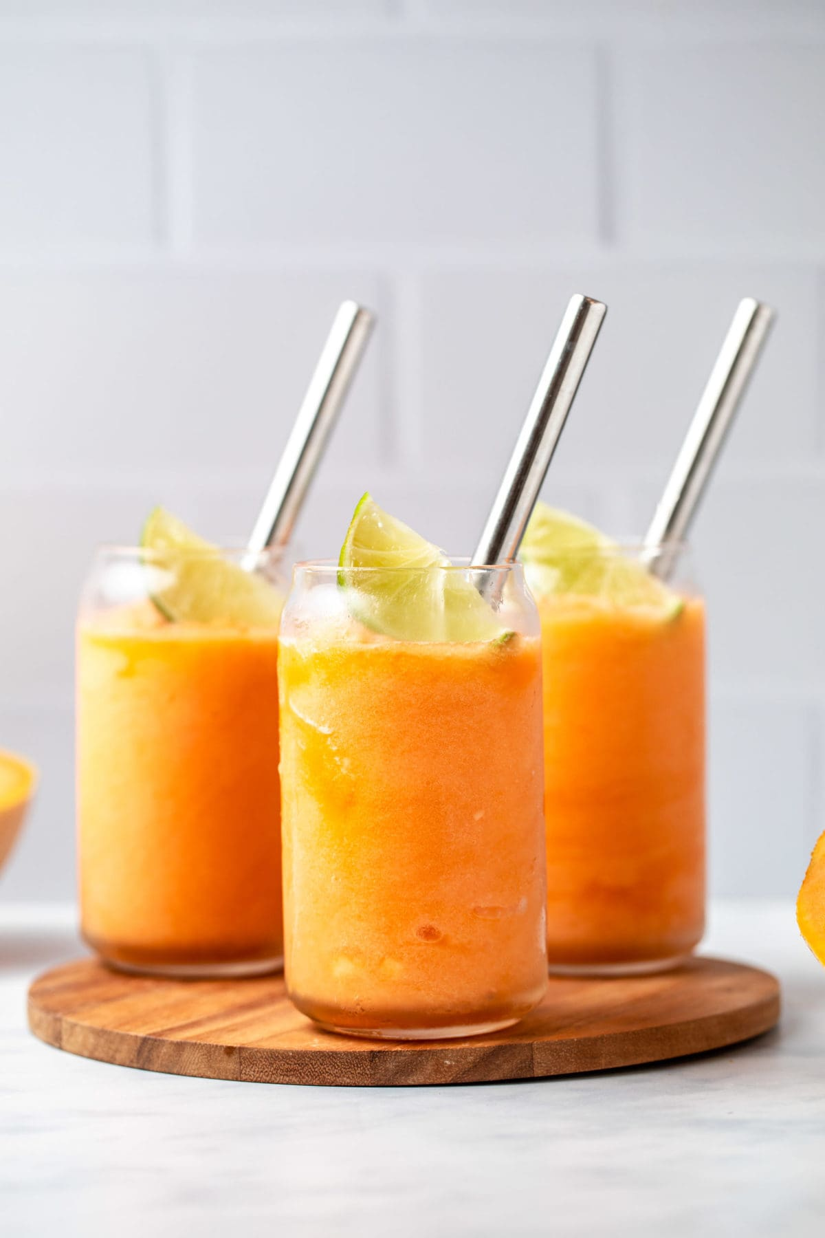 3 glasses of cantaloupe slushie topped with a lime wedge and a metal straw