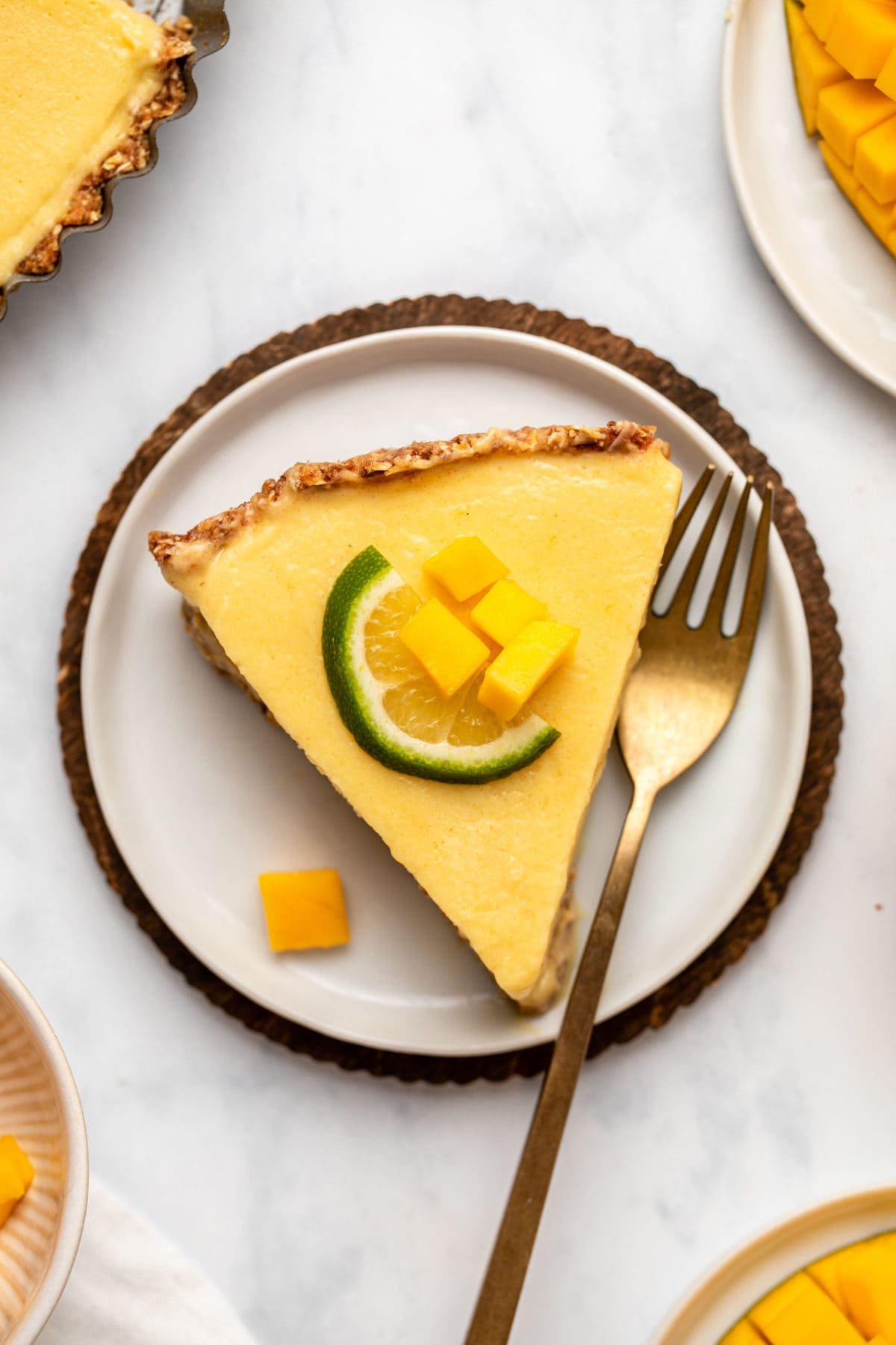 Slice of mango tart topped with lime slice on marble background