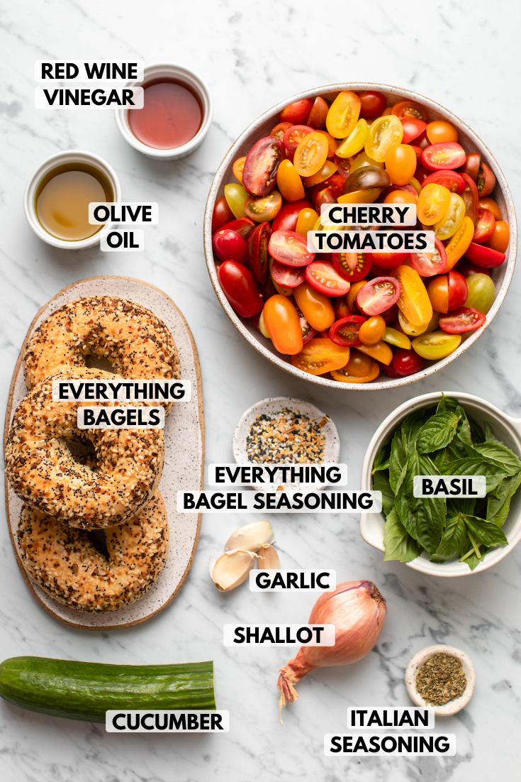Ingredients for Everything Bagel Panzanella Salad in small white bowls on marble background. Clockwise text labels read cherry tomatoes, everything bagel seasoning, basil, garlic, shallot, italian seasoning, cucumber, everything bagels, olive oil, red wine vinegar