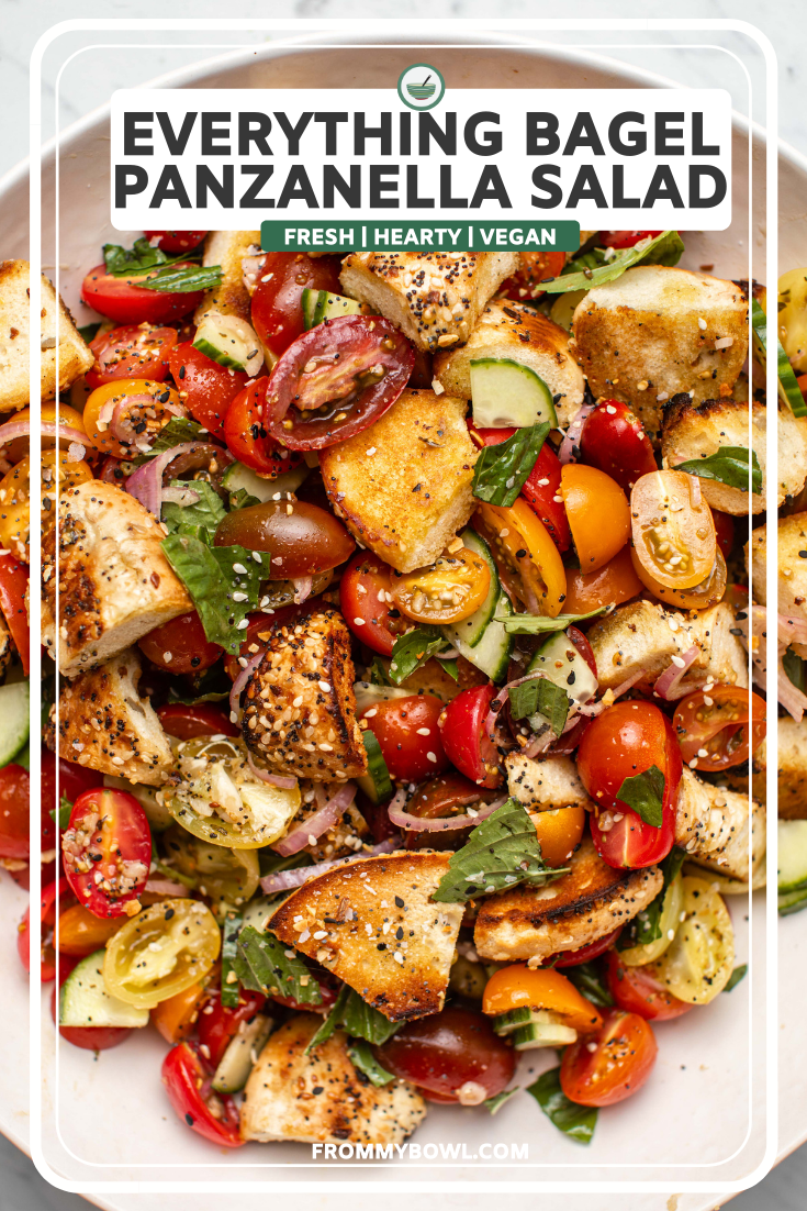 Everything bagel panzanella salad with colorful tomatoes and fresh basil in large white bowl