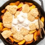 Grilled peach cobbler in cast iron pan with melted vanilla ice cream on top