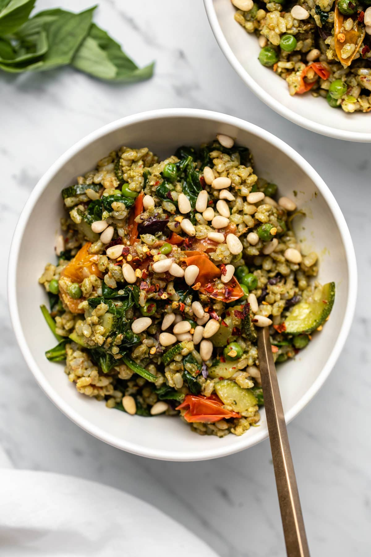 Close up photo of pesto fried rice with colorful cooked tomatoes in a small white bowl topped with pine nuts and a gold fork