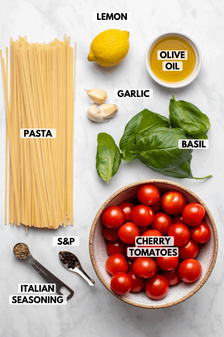 Ingredients for roasted cherry tomato pasta arranged on marble countertop; clockwise text labels read lemon, olive oil, garlic, basil, cherry tomatoes, salt & pepper, italian seasoning, and pasta