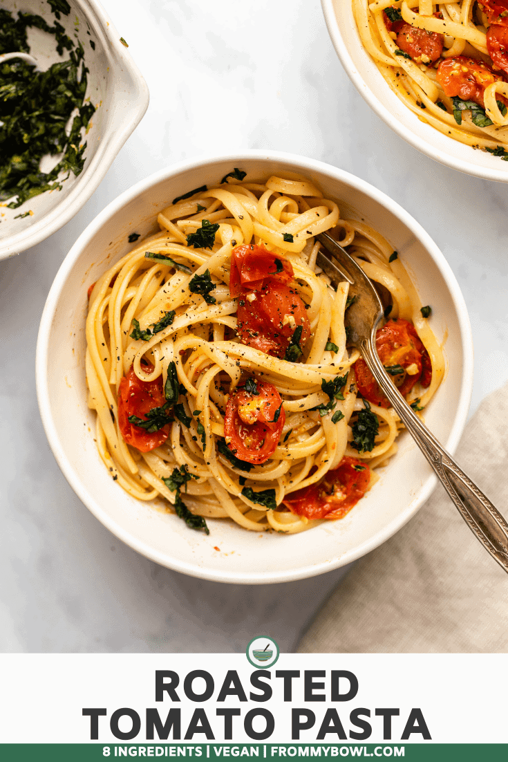 Roasted tomato pasta with basil gremolata in white bowl with silver fork on marble background