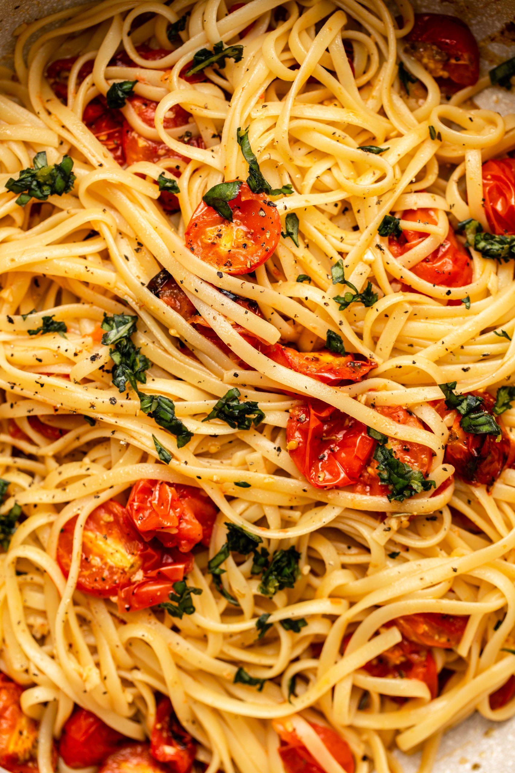 up-close photo of roasted cherry tomato pasta with fettucine and basil gremolata