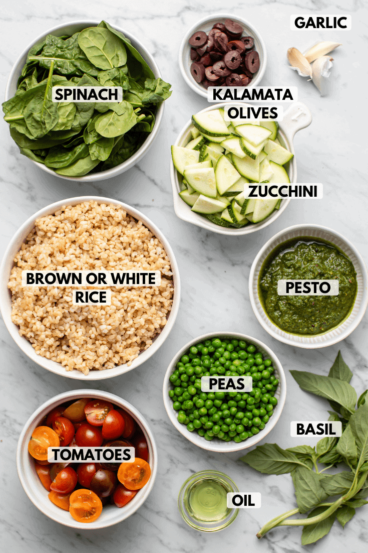 Ingredients for pesto fried rice in small white bowls on a marble countertop. Clockwise ingredient labels read garlic, zucchini, pesto, peas, basil, oil, tomatoes, brown or white rice, spinach, and kalamata olives