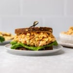 Buffalo chickpea salad in a sandwich with lettuce on a small plate, on a marble background
