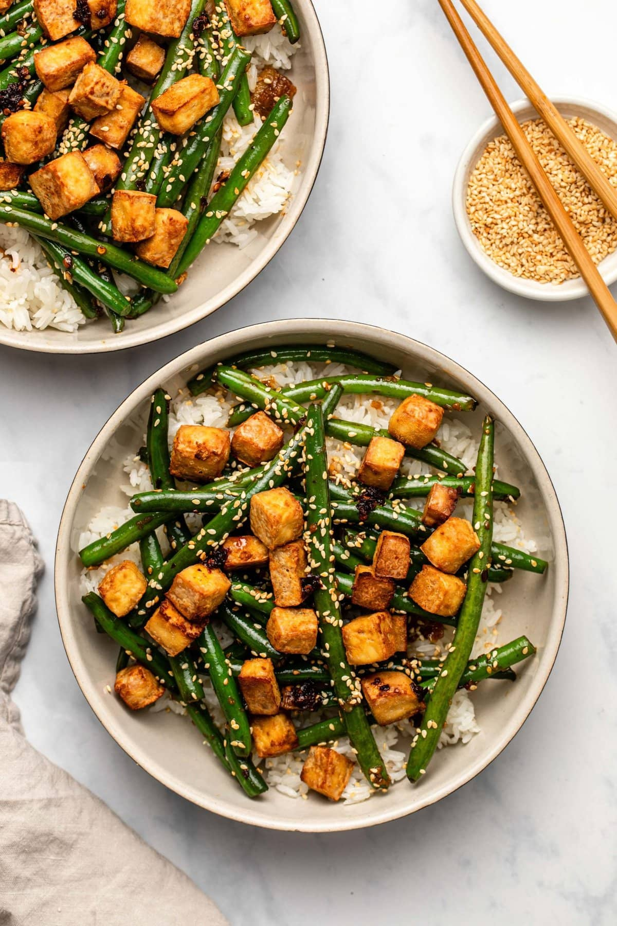 Two large bowls of garlic green bean stir fry with crispy tofu over white rice. A small bowl of toasted sesame seed sits off to the side with a pair of wooden chopsticks