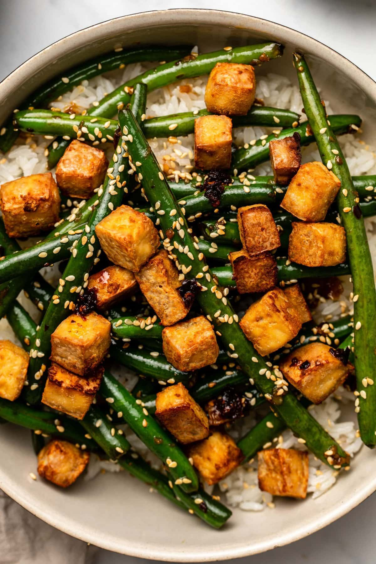 close-up overhead photo of green beans and crispy tofu over white rice