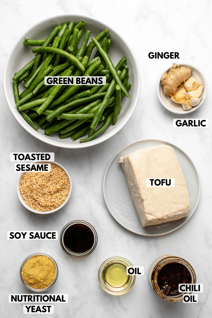 Ingredients for green bean stir fry in small bowls on marble background. Clockwise text labels read ginger, garlic, tofu, chili oil, oil, nutritional yeast, soy sauce, toasted sesame, and green beans