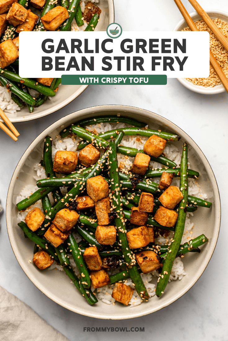 Garlic Green Bean Stir Fry with Crispy Tofu over white rice in large bowl on marble background