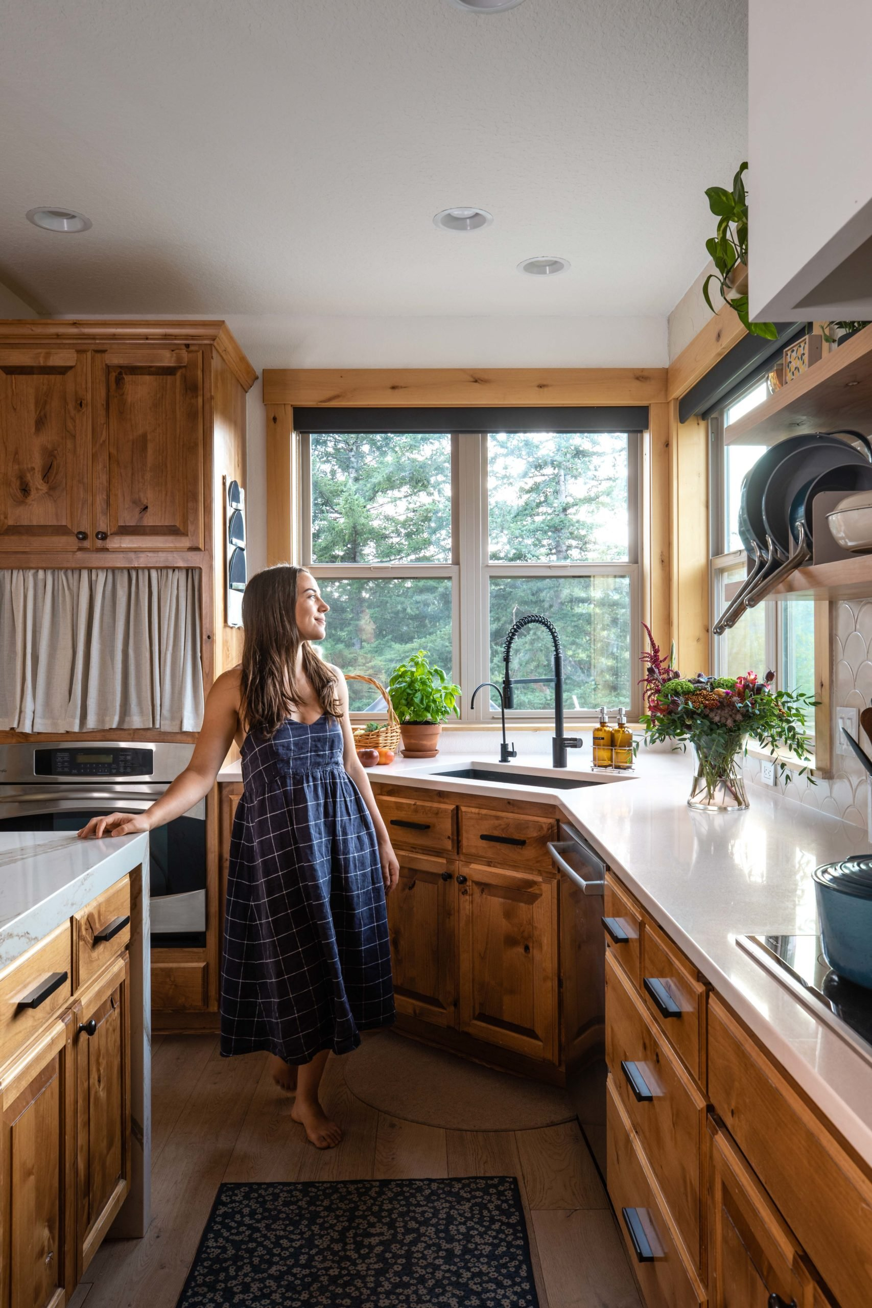 Caitlin standing in the kitchen looking out at a window full of pine trees