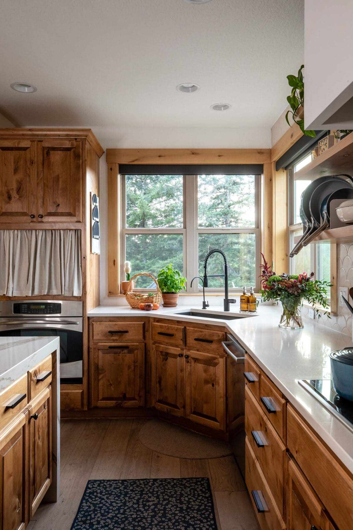 Shot of corner sink with light filled windows with pine trees in the background