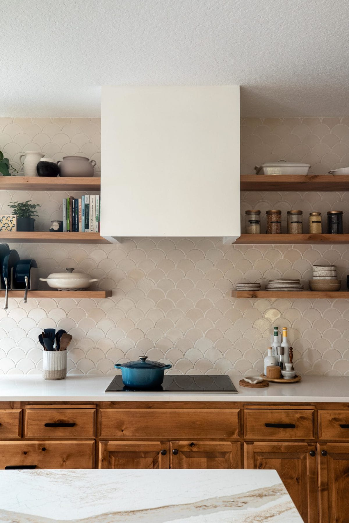 Cozy warm kitchen show with a white vent hood, tile backsplash, and open shelving