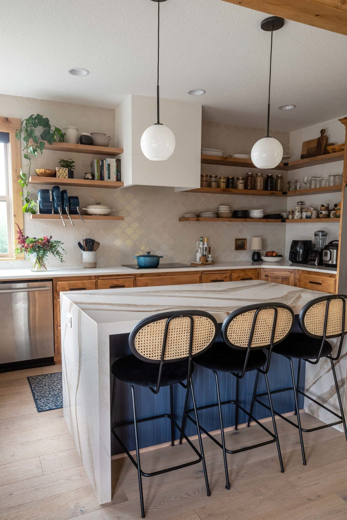 Side angle view of kitchen with waterfall island, cane counter stools, a full tile backsplash, and wood floating shelves filled with various items