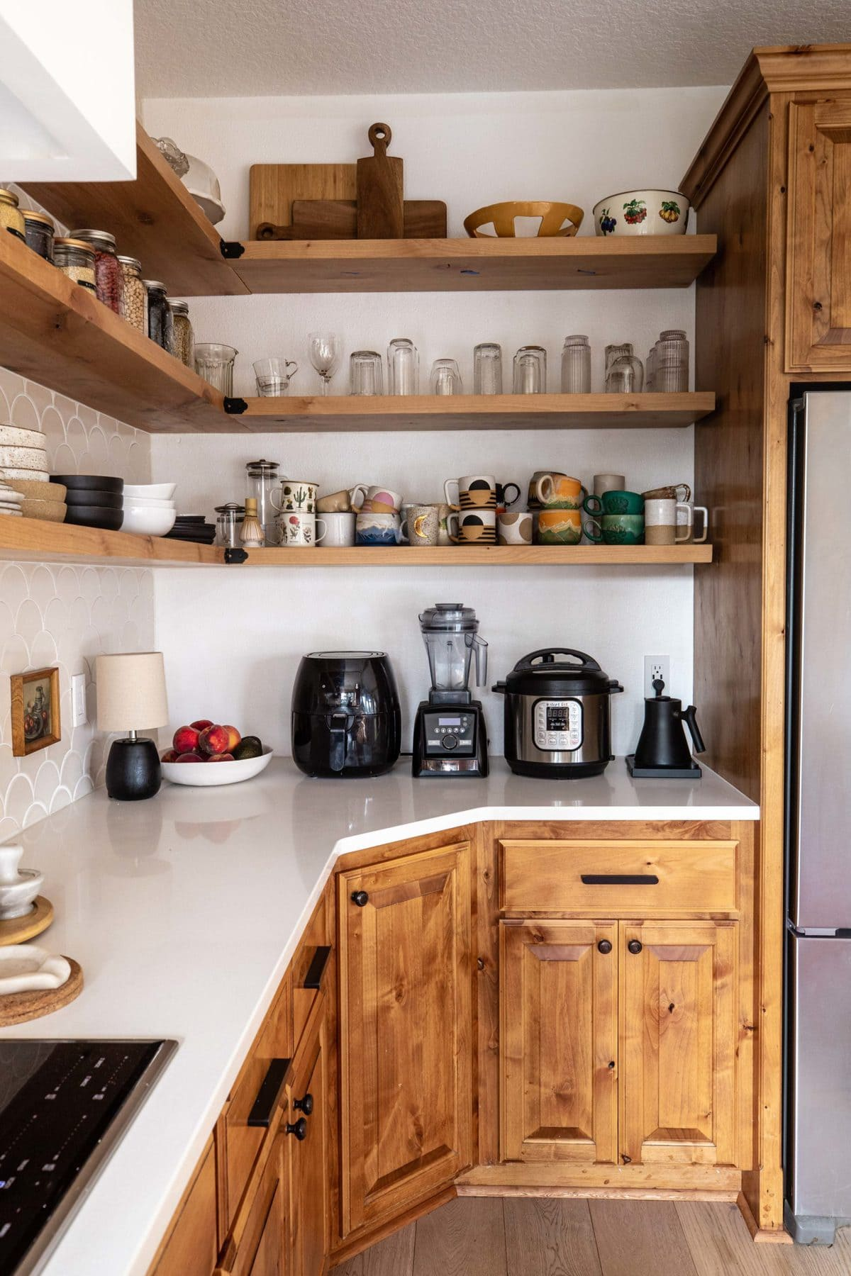 small kitchen nook with wood cabinets and a white countertop with a ceramic mug collection and glasses resting on floating shelves
