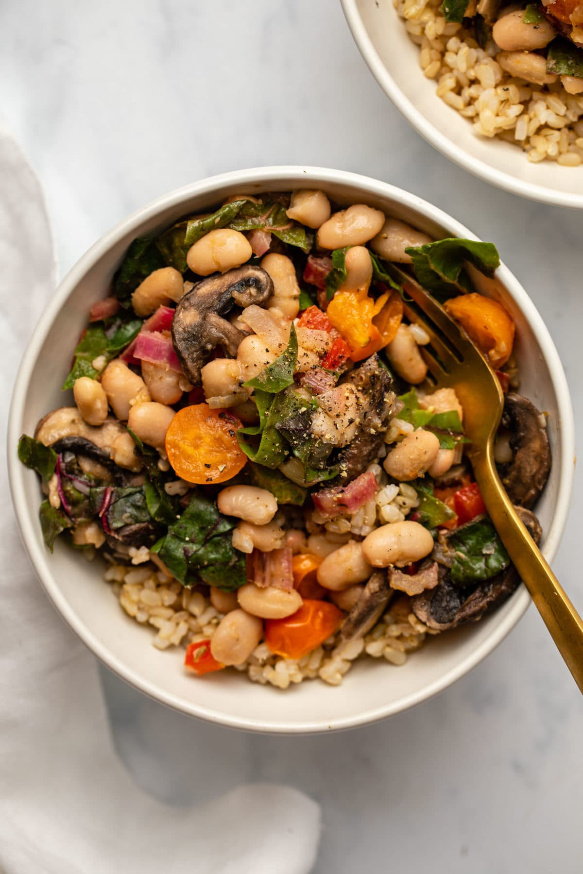 Summer white bean stir fry in white bowl with gold fork
