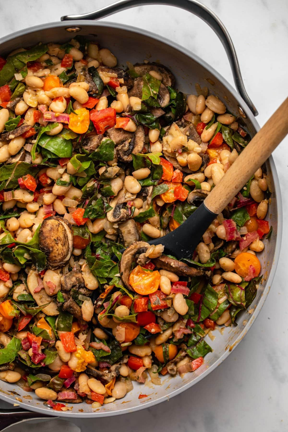 White bean stir fry with vegetables in large sauté pan with wooden spoon