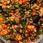 Large sauté pan of white bean skillet with colorful sauteed summer vegetables