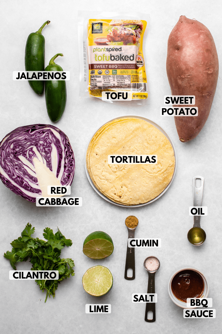 Ingredients for tacos arranged on marble background. Clockwise text labels read sweet potato, tortillas, oil, bbq sauce, salt, cumin, lime, cilantro, red cabbage, jalapeno, tofu