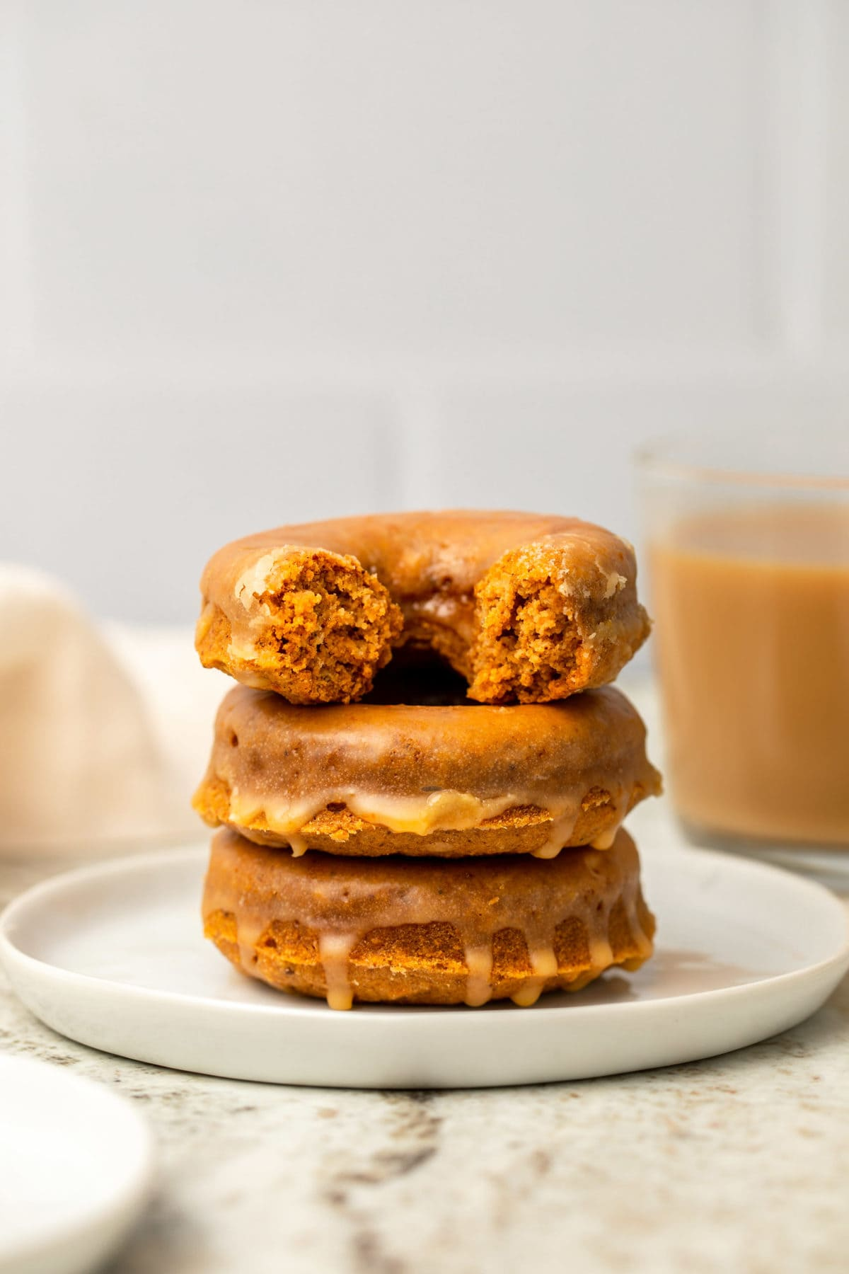 Stack of pumpkin chai spiced donuts topped with glaze on white plate with chai in the background
