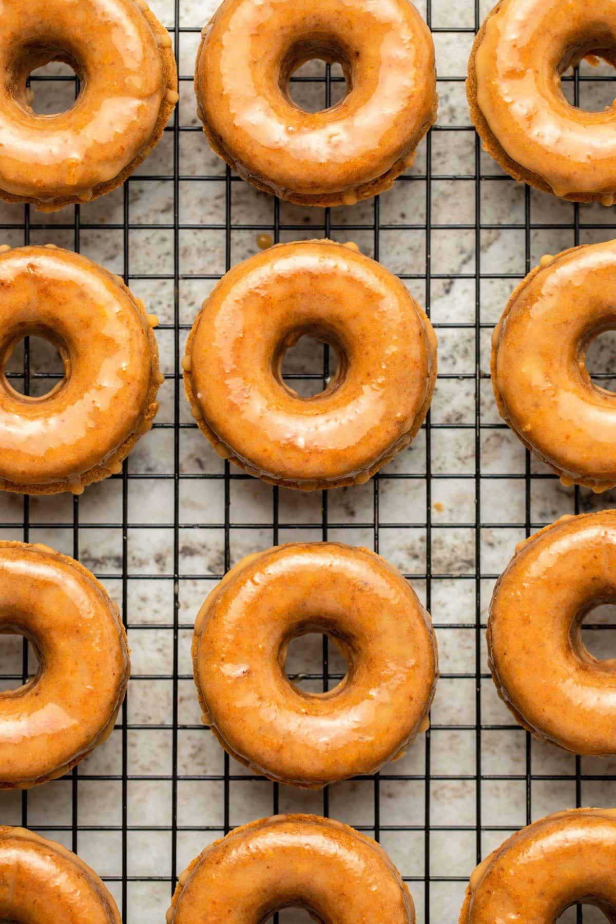 glazed pumpkin donuts on cooling rack