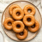 Glazed pumpkin chai spiced donuts on tan plate on stone background