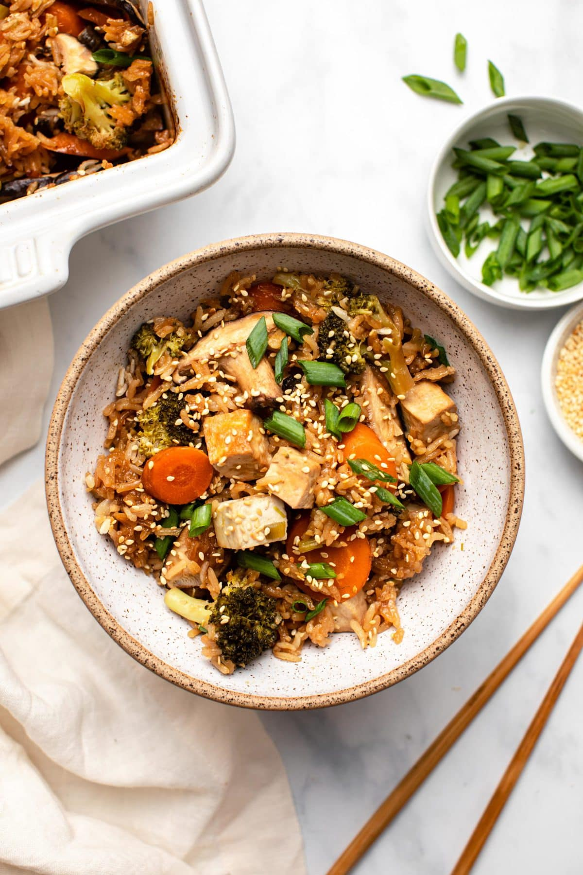 Teriyaki Tofu Casserole in white bowl topped with green onion and sesame seeds next to small bowls of green onion and sesame seeds