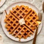 Pumpkin spice waffle topped with powdered sugar, maple syrup, and vegan butter on a speckles white plate on stone background