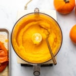 Homemade Pumpkin Puree in food processor with roasted pumpkin skins and fresh pumpkins off to either side
