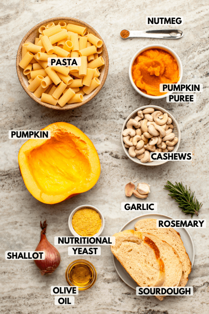 Ingredients for baked pumpkin mac and cheese in small white bowls on marble background. Clockwise text labels read nutmeg, pumpkin puree, cashews, garlic, rosemary, sourdough, olive oil, shallot, nutritional yeast, pumpkin, and pasta