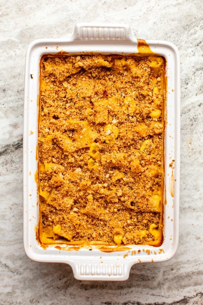 Baked Vegan Pumpkin Mac & Cheese in white casserole dish on stone background