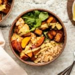 Small bowl with brown rice, arugula, roasted sweet potato, roasted cauliflower, and roasted tofu drizzled with curry tahini dressing on stone background
