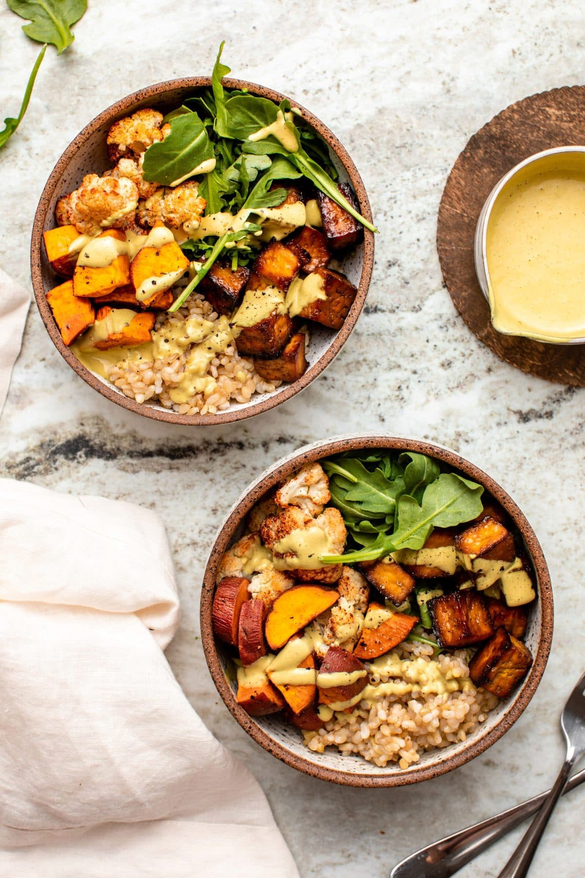 Two side-by-side nourish bowls topped with curry tahini dressing on stone background
