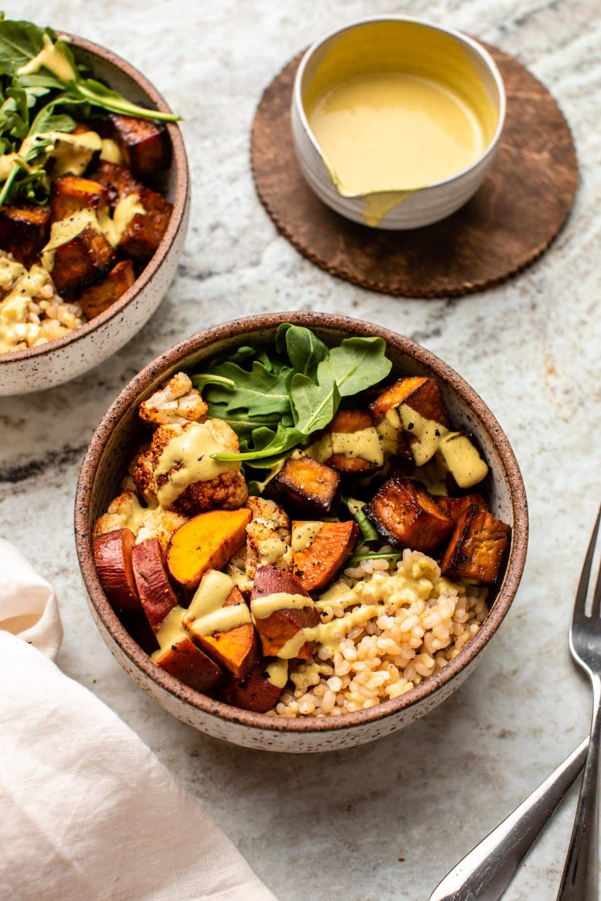 Photos of two nourish bowls and a small bowl of dressing off to the side