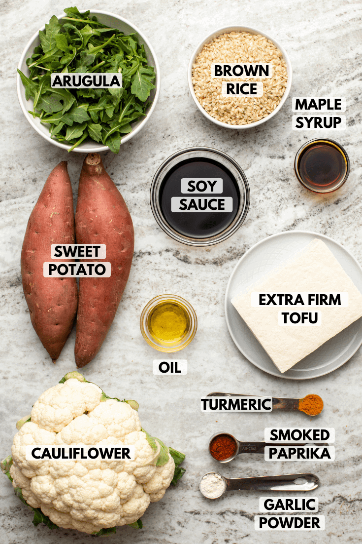 Ingredients for nourish bowls with maple turmeric tofu in small bowls on stone background. Clockwise text labels read brown rice, maple syrup, extra firm tofu, turmeric, smoked paprika, garlic powder, cauliflower, oil, sweet potato, arugula, and soy sauce