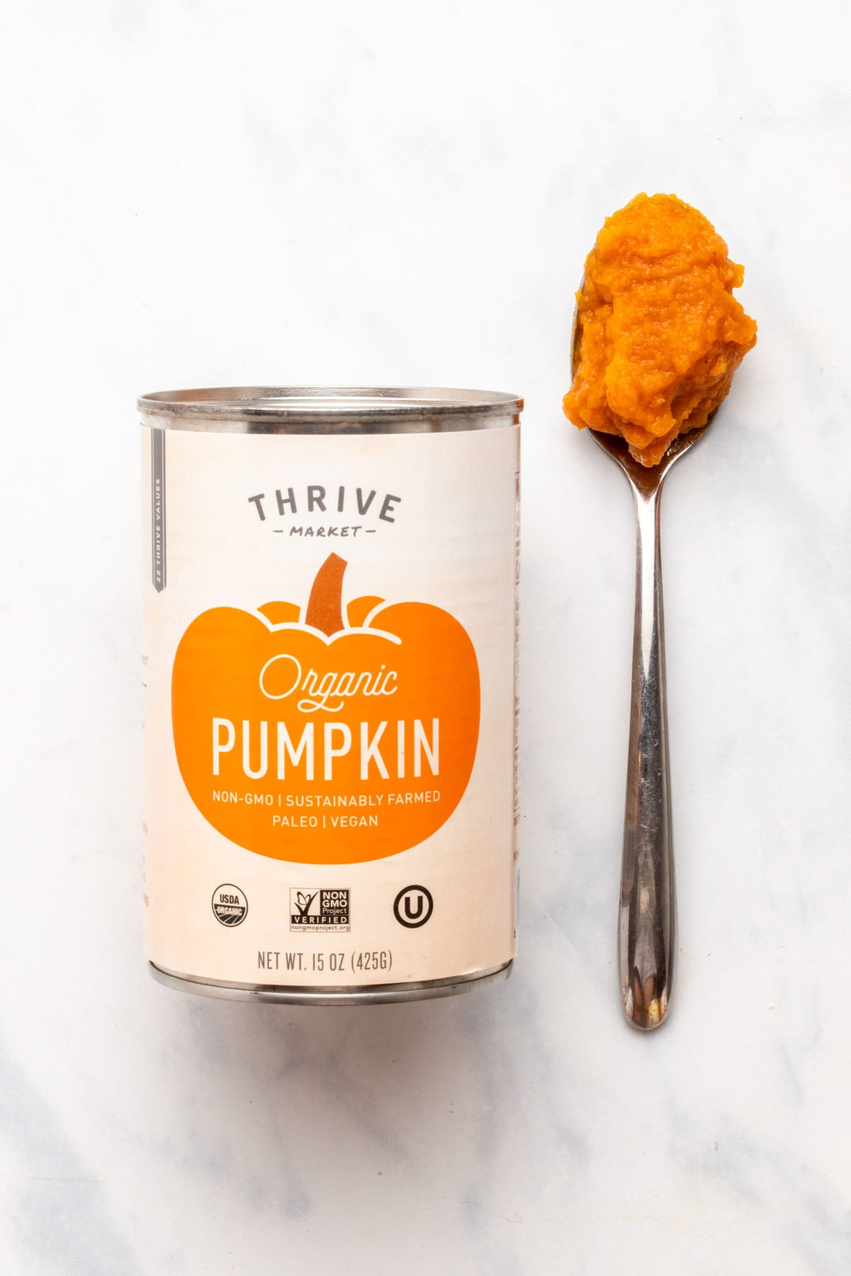 Can of Thrive Market pumpkin puree next to spoon with puree on it