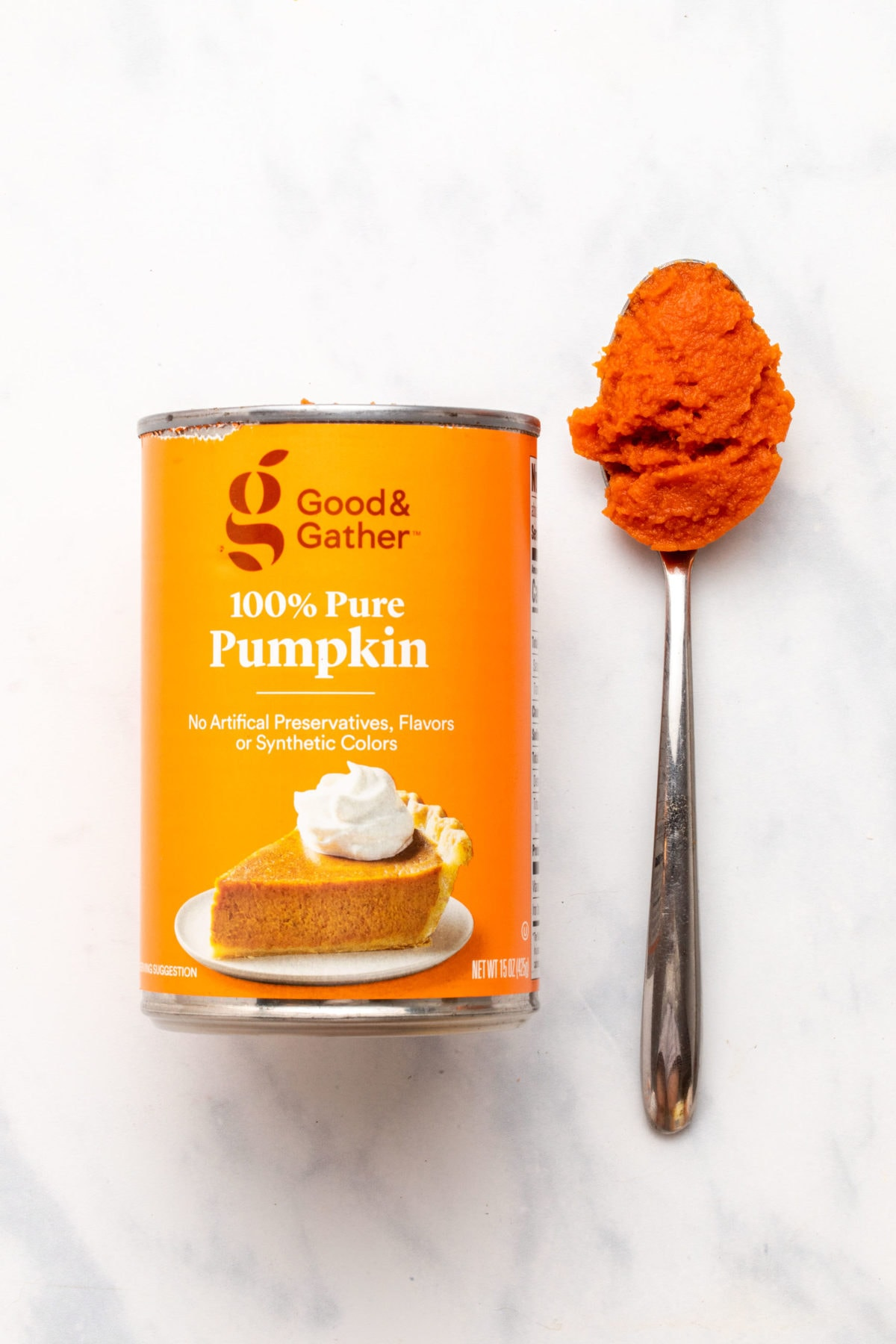 Can of Target's Good & Gather pumpkin puree next to spoon with puree on it