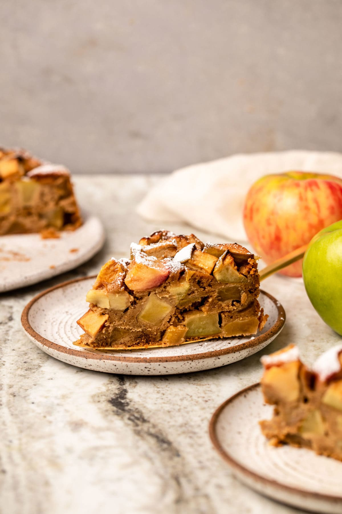 slice of apple cake on plate surrounded by fresh apples